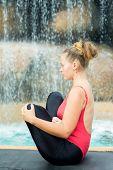 Woman practicing yoga near waterfall. Fetus Pose. Garbhasana