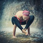 Woman practicing yoga near waterfall. Shoulder pressing posture. Bhujapidasana