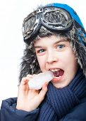 Kid wearing winter clothes trying to eat icicle on white background