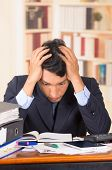 pic of overwhelming  - young stressed overwhelmed business man holding head with his hands looking at piles of folders on his desk  - JPG