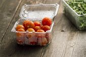 cherry tomatoes in plastic dishes and arugula