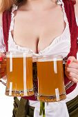 big breasts Oktoberfest waitress with two mugs of beer