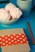 Delicate Pink Marshmallows In The Blue Plate, Old Notebook And Cup On Blue Background