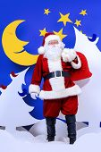 Santa Claus standing with his bag of giftsin a cartoon fairy snowy forest. Full length portrait.