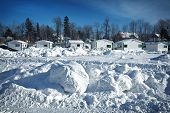 Fishing huts in the snow at Ste-Anne De La Perade in Quebec province, Canada. A village of small huts are assembled on the frozen river each year for the ice fishing season.