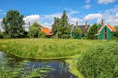 Small creek and rural wooden houses on green banks in Zaanse Schans - famous dutch village.