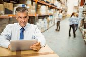 Manager working on tablet pc while looking at camera in a large warehouse