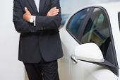Close up of businessman standing with arms crossed at new car showroom