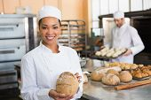 Pretty baker smiling at camera with loaf in the kitchen of the bakery