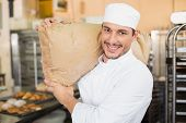 Smiling baker holding bag of flour in the kitchen of the bakery