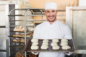 Smiling baker holding tray of raw dough in the kitchen of the bakery
