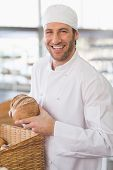 Happy baker with loaf of bread in the kitchen of the bakery
