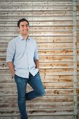 Smiling casual man standing against faded pine wooden planks
