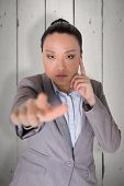 Thoughtful asian businesswoman pointing against white wood