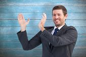 Smiling businessman showing something with his hands against wooden planks