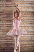 Pretty ballerina in pink against wooden planks