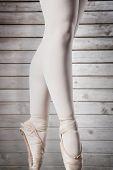 Ballerina standing en pointe against wooden planks
