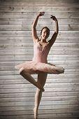 Pretty ballerina dancing against wooden planks background