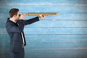 Businessman looking through telescope against wooden planks