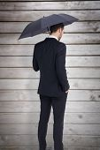 Thoughtful businessman under umbrella with hand in pocket against wooden planks