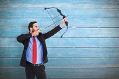 Focused businessman shooting a bow and arrow against wooden planks