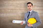 Serious architect holding plans and hard hat against wooden surface with planks