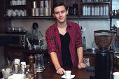 Young barista  at cofeeshop cafe made a cup of coffee and smile charming.