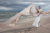 pic of long beach  - female model in long beige dress posing dynamic in the beach - JPG