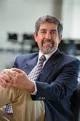 Mature Hispanic businessman smiling inside office building