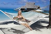 the beautiful woman in a long sundress in a hammock on a sea background