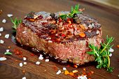stock photo of chili peppers  - grilled steak with thyme on wooden board - JPG