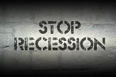 image of stagnation  - stop recession stencil print on the grunge white brick wall - JPG