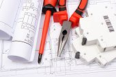 pic of electrical engineering  - Rolled electrical diagrams electric fuse and work tools lying on construction drawing of house drawings for the projects engineer jobs - JPG