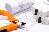 foto of electrical engineering  - Rolled electrical diagrams electric fuse and work tools lying on construction drawing of house drawings for the projects engineer jobs - JPG