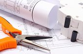 stock photo of electrical engineering  - Rolled electrical diagrams electric fuse and work tools lying on construction drawing of house drawings for the projects engineer jobs - JPG