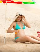 picture of suntanning  - Happy pregnant woman in bikini applying suntan creme - JPG