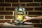 stock photo of kerosene lamp  - Hand lights a kerosene lamp on brick wall background - JPG