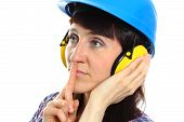 picture of silence  - Female construction worker wearing protective helmet and headphones holding index finger to lips and showing silence sign safety at work and ear protection - JPG