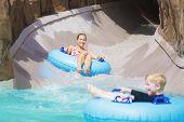 stock photo of wet  - Family enjoying a wet ride down a water slide - JPG