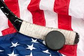 stock photo of inference  - Hockey equipment including a stick and puck on an American flag to infer a patriotic American sport - JPG