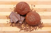 pic of chocolate muffin  - Delicious fresh baked chocolate muffins grated chocolate and portion of chocolate lying on wooden cutting board - JPG