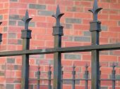 Iron Fence By Brick Wall