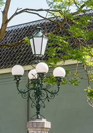 stock photo of light fixture  - Restored historic lighting from 1896 at the entrance to an old park in the Netherlands - JPG