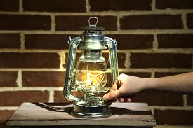 stock photo of kerosene lamp  - Hand lights a kerosene lamp on brick wall background - JPG