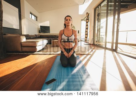 Young Woman Practicing Yoga Indoors, Vajrasana.