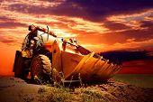 Tractor amarillo en el cielo de oro surise