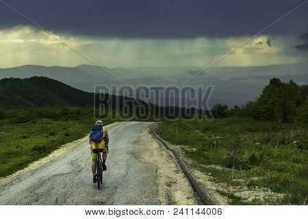 poster of Man Travel Alone By Bicycle In Rainy Landscape. Traveler Cycle On Mountain Road Enjoying Beautiful M