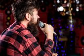 Man In Checkered Shirt Holds Microphone, Singing Song, Karaoke Club Background. Guy Likes To Sing In poster