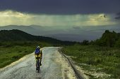 Man Travel Alone By Bicycle In Rainy Landscape. Traveler Cycle On Mountain Road Enjoying Beautiful M poster