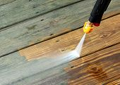 image of pressure  - A pressure washer cleaning a wood deck - JPG
